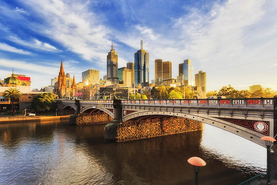 Warm bright sunlight lit Melbourne city over Princes bridge St Kilda road sun sunrise over waters of Yarra river.
