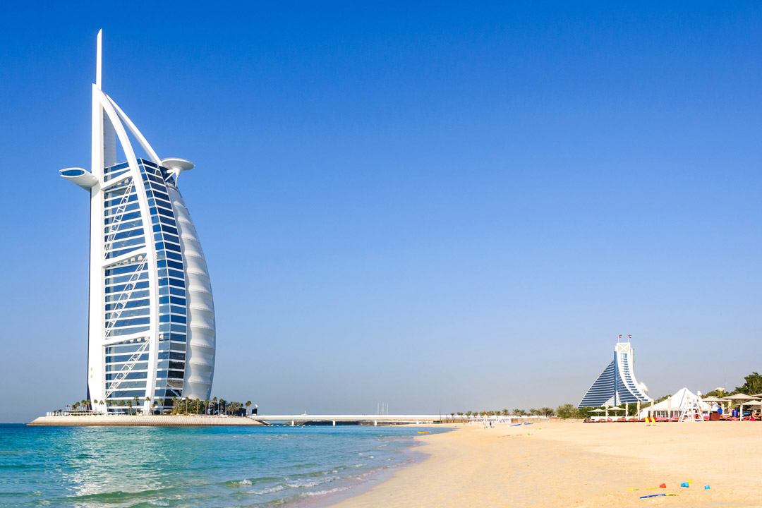 Burj al Arab on the left of the image with beach and sea filling the rest of the space