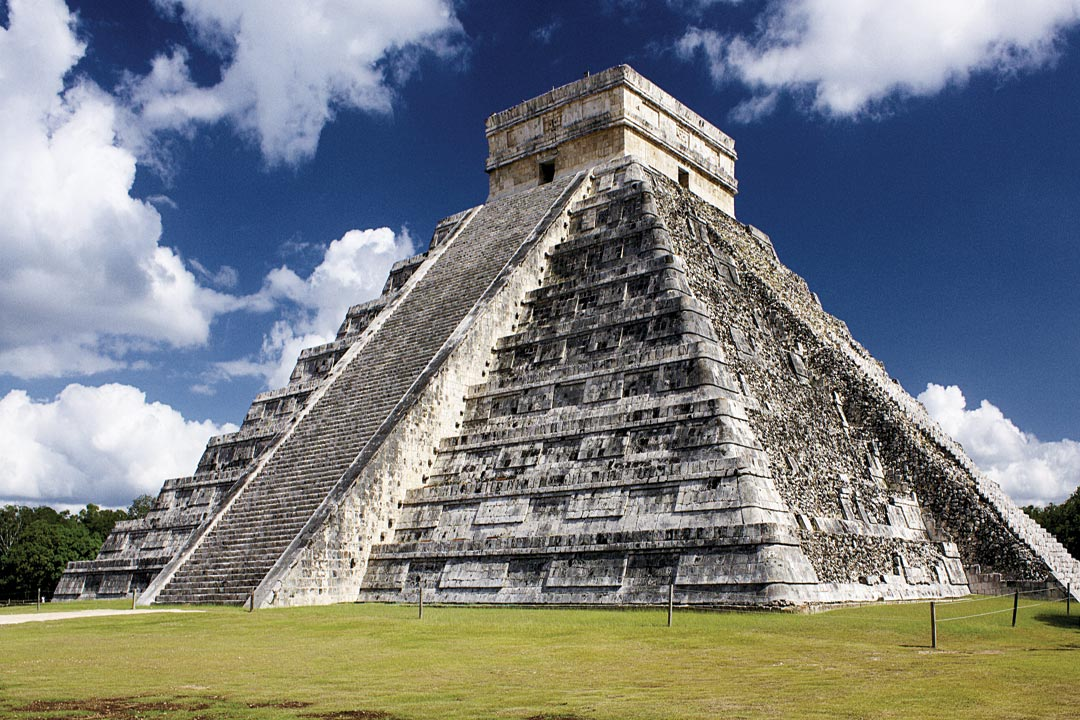 The giant pyramid at Chichen Itza on flat, green grass with blue skies in the background.