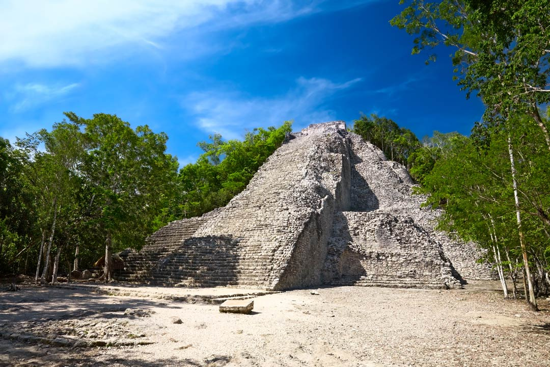 An old pyramid ruin at Coba with lush vegetation in the background.