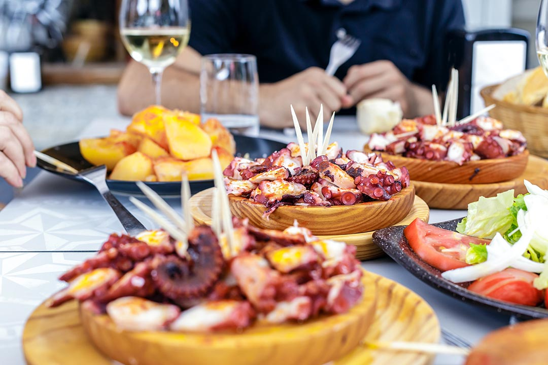 People eating Pulpo a la Gallega with potatoes.