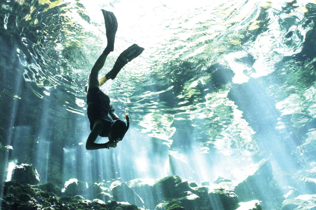 A snorkeller swimming through baby blue water with light streams coming through.