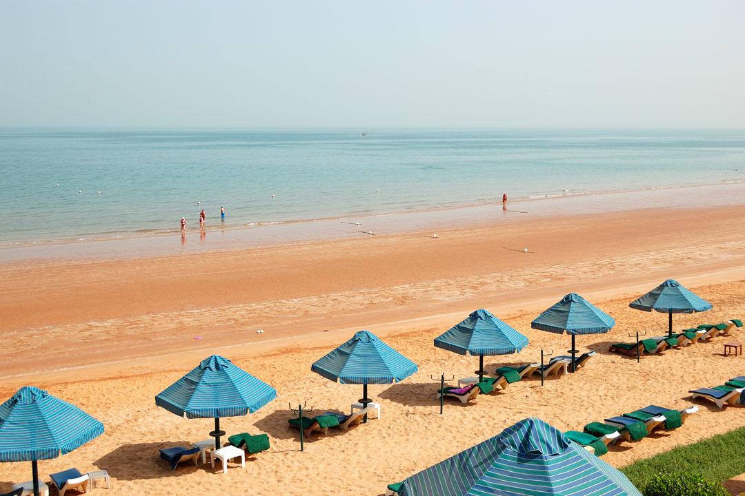 An aeiral view of a white sand beach with parasol shades in Ras Al Khaimah.