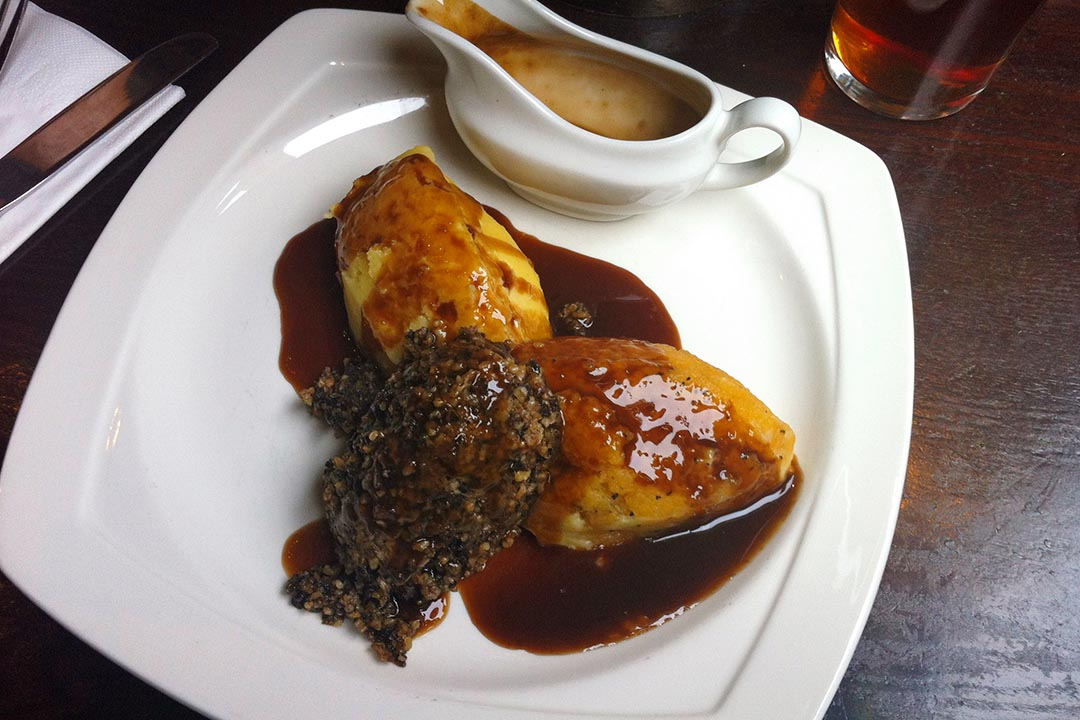 Ceramic plate of haggis, neeps, and tatties with beef gravy, and a glass of beer, on top of a wooden pub table.
