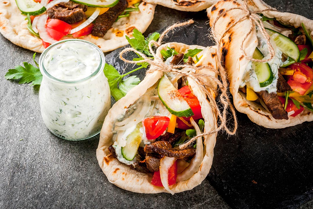 Traditional Greek wrapped sandwich gyros - tortillas, bread pita with a filling of vegetables, beef meat and sauce tzatziki on a black stone table.