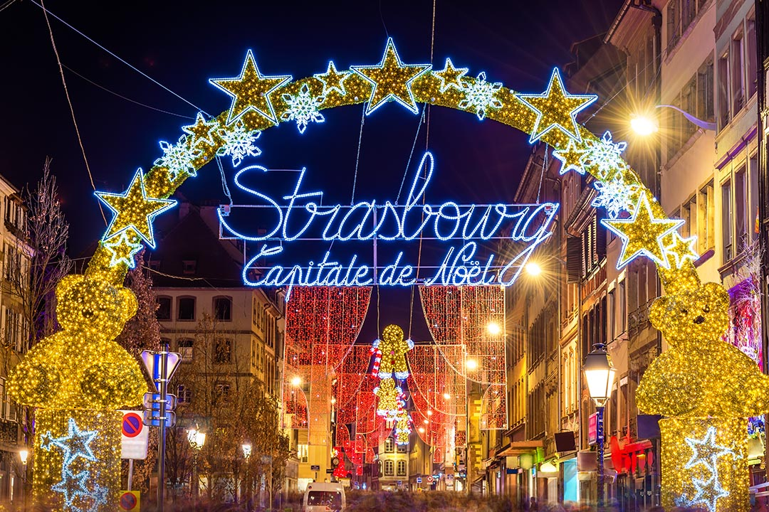 Entrance to the city centre of Strasbourg on Christmas time, an archway of christmas lights adorned with gold stars.