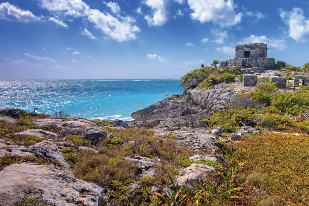 The mayan ruins of Tulum on a hill looking over the turquoise water of the Mayan Riviera.