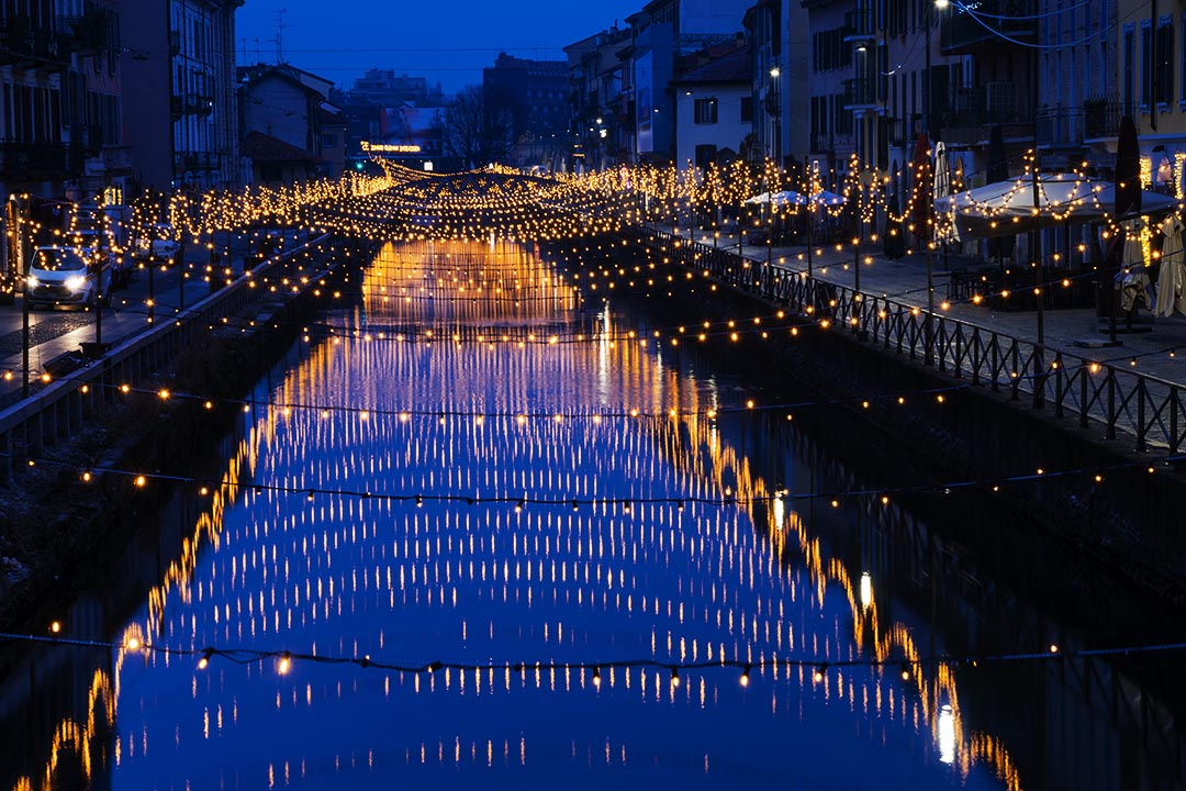 Milan, Italy: The Naviglio Grande canal waterway with orange fairy lights, night view.