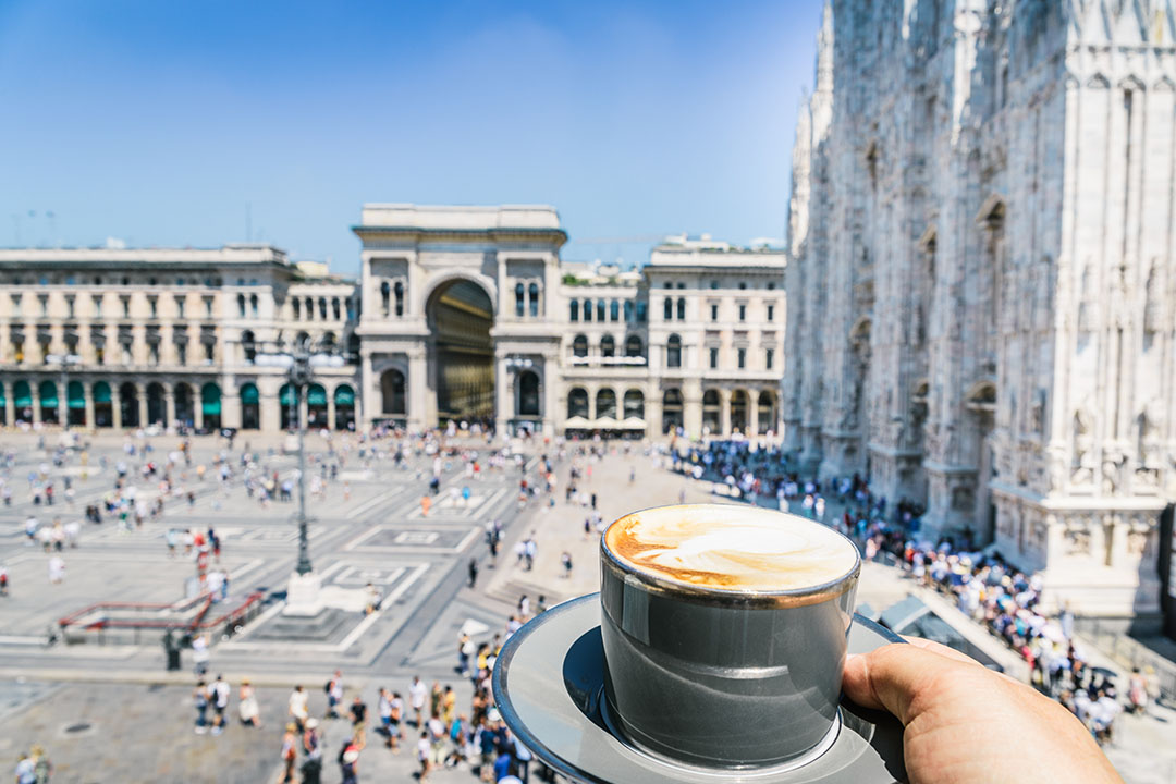 A cappuccino held in front of a view of galleria vittorio emanuele ii