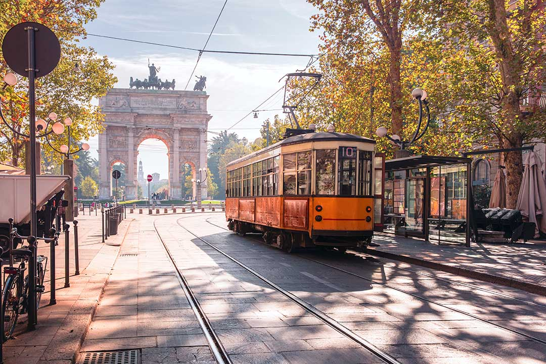 Famous vintage tram in the centre of the Old Town of Milan in the sunny day, Lombardia, Italy. Arch of Peace, or Arco della Pace in the background.