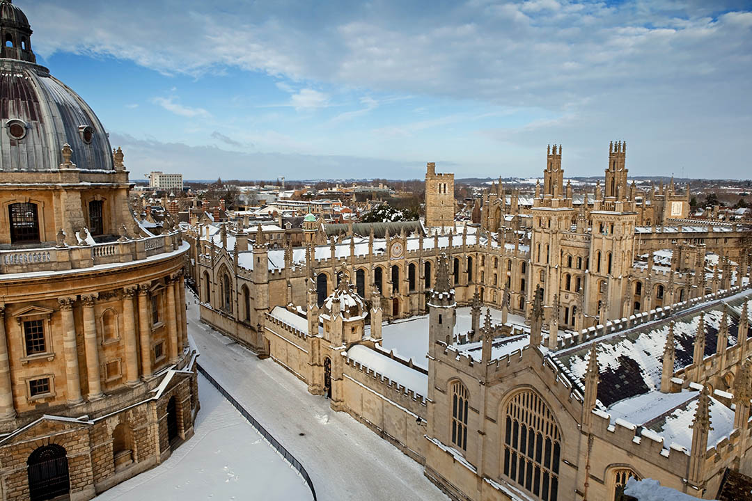 Snowy view of Oxford colleges, with the grand buildings and a courtyard coated in a sprinkling of snow