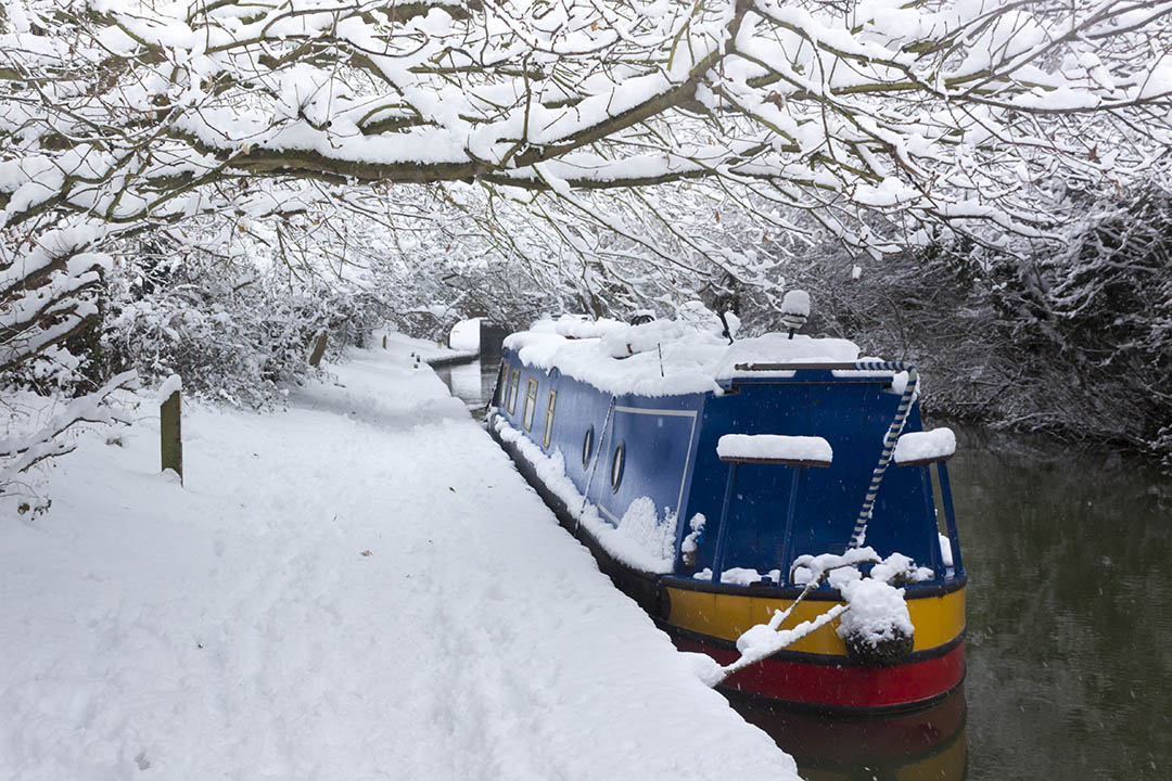 Winter scene of snow around a canal and a snow topped canal boat