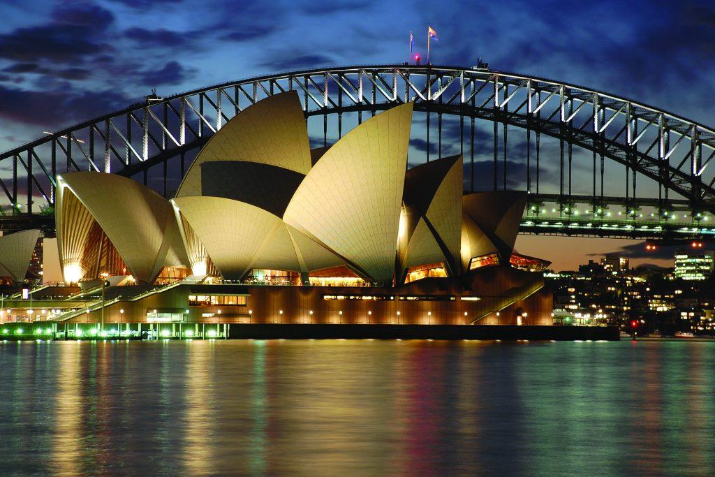 The Sydney Opera House lit up against a dusky sky.