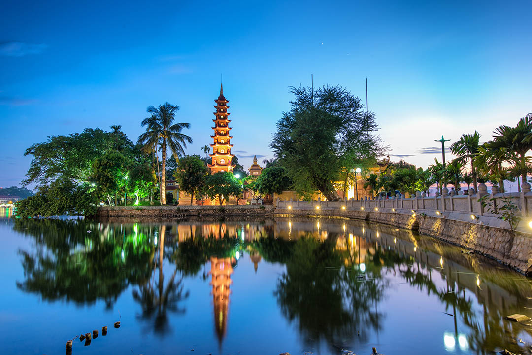 Tran Quoc Pagoda light up at night, reflected on the water.