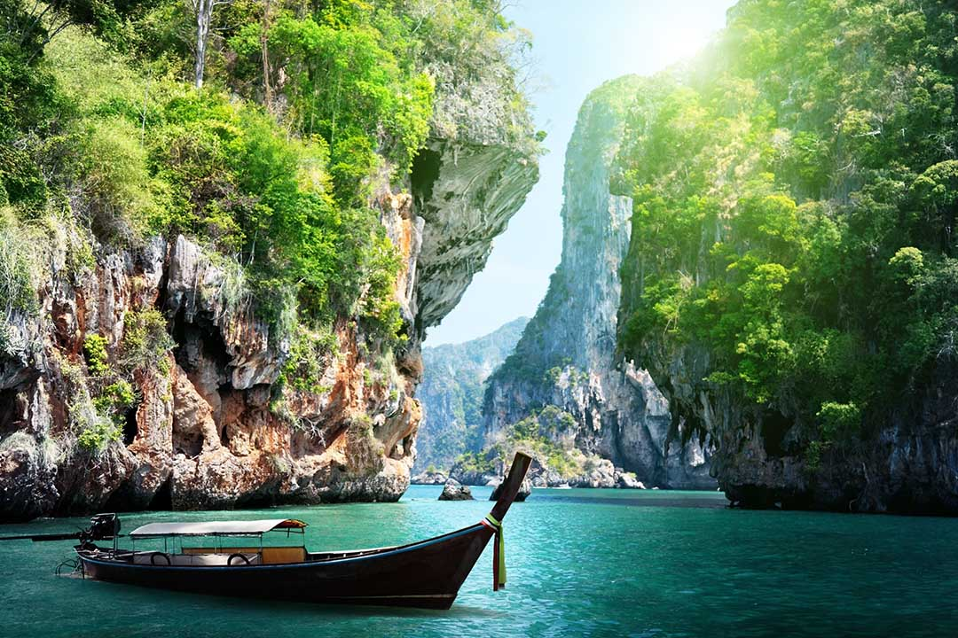 A long boat sits peacefully on the blue waters of Halong Bay, with giant rock formations in the background.