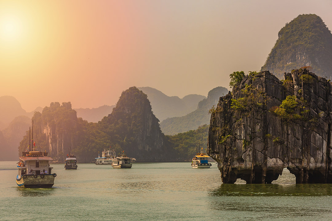 Halong Bay at dusk, and an orange sky with boats dotted on the water.