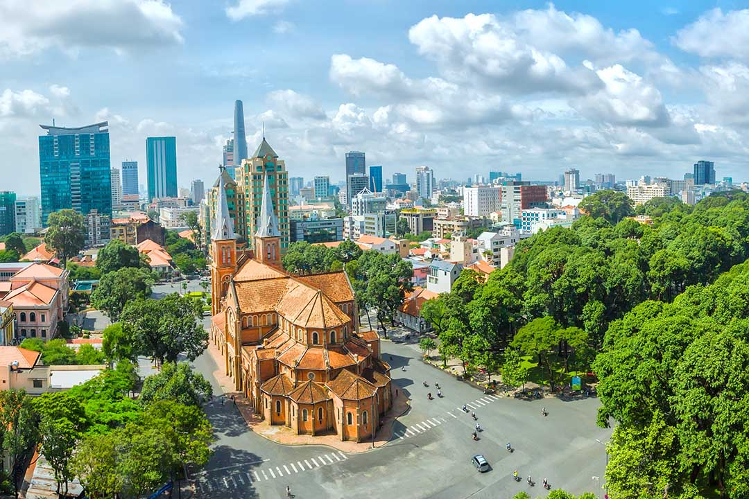 Ho Chi Minh cathedral surrounded by greenery and the city in the background.