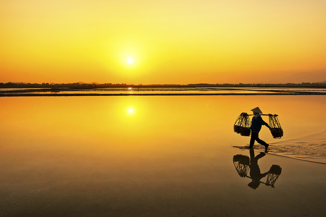 A worker crossing the salt fields during sunset.