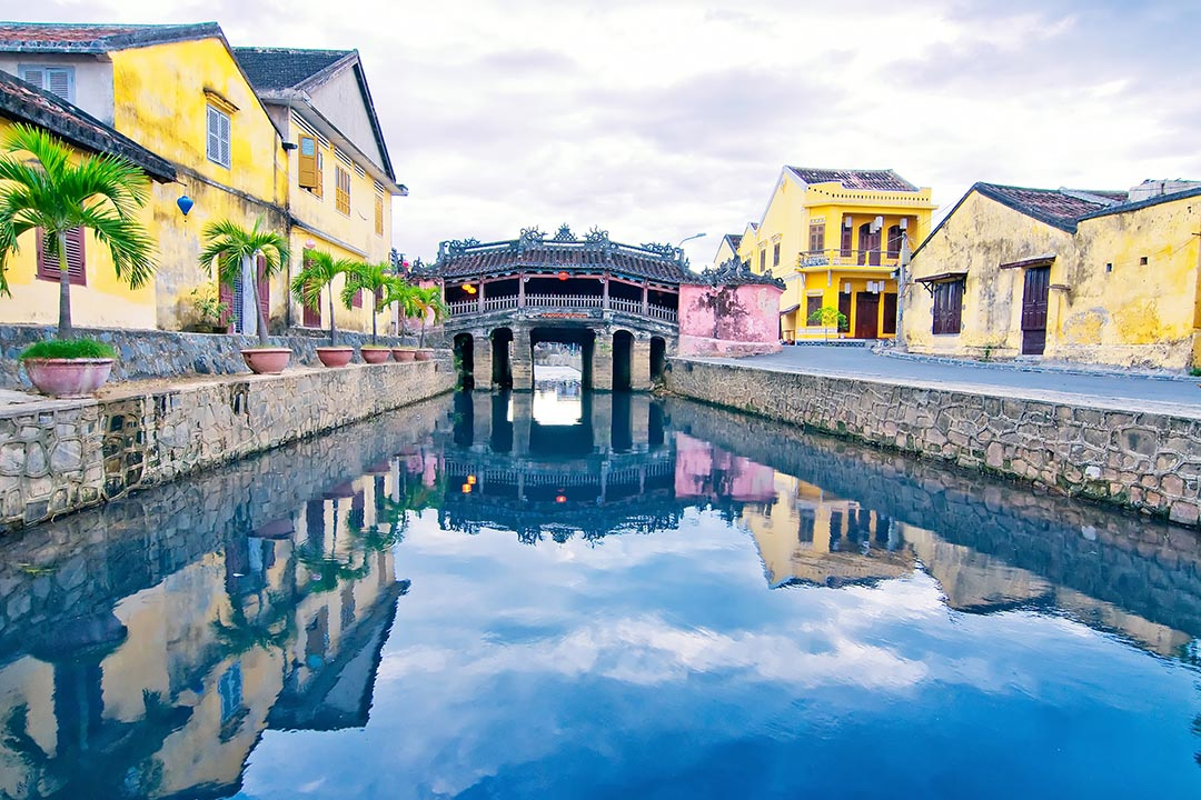 A river through Hoi An surrounded by bright yellow buildings, leading to a bridge.