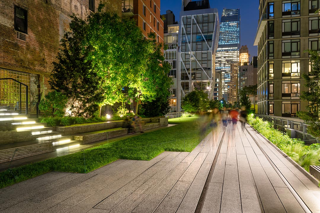 The High Line promenade illuminated at twilight surrounded by modern and older buildings in Chelsea. The aerial greenway is also known as Highline or High Line Park. Manhattan, New York City.