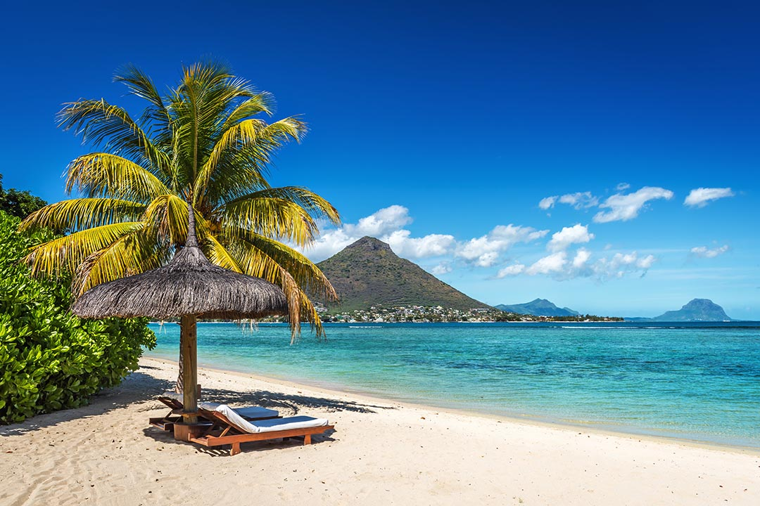 Loungers and umbrella on tropical beach on Mauritius Island in the Indian Ocean.