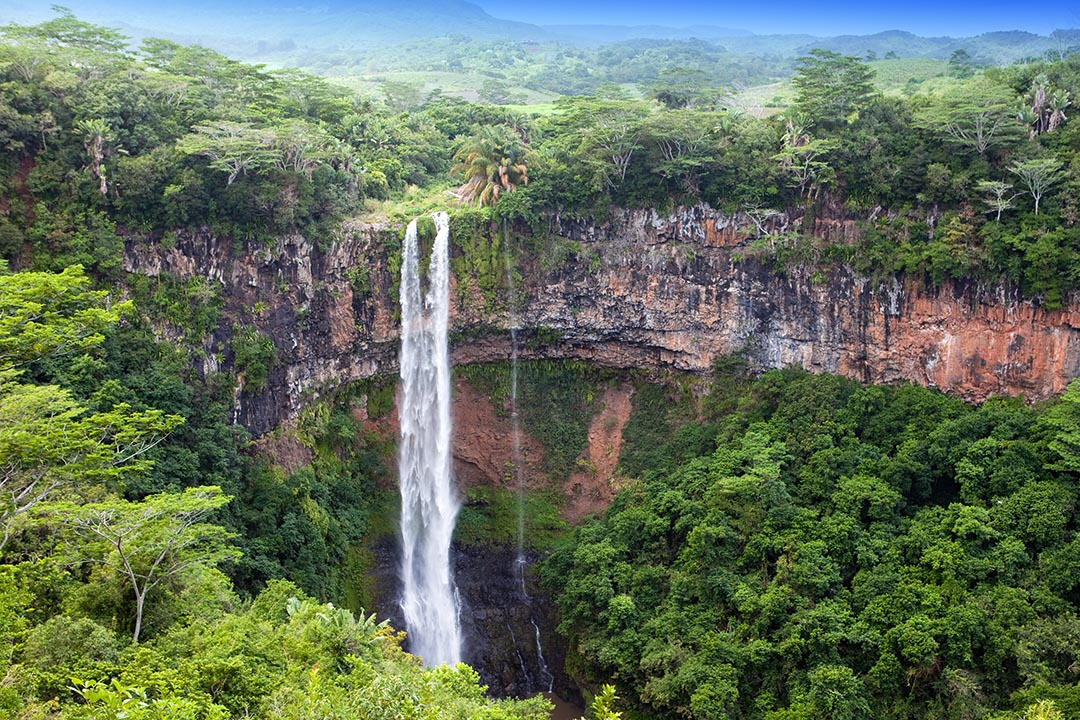 Chamarel waterfalls in Mauritius. A tall, narrow, tumbling waterfall surrounded be green trees.