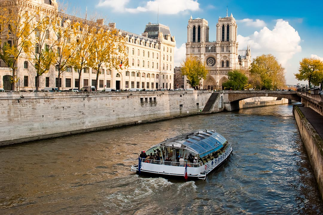 A boat cruising down the River Seine and past the Notre Dame Cathedral.
