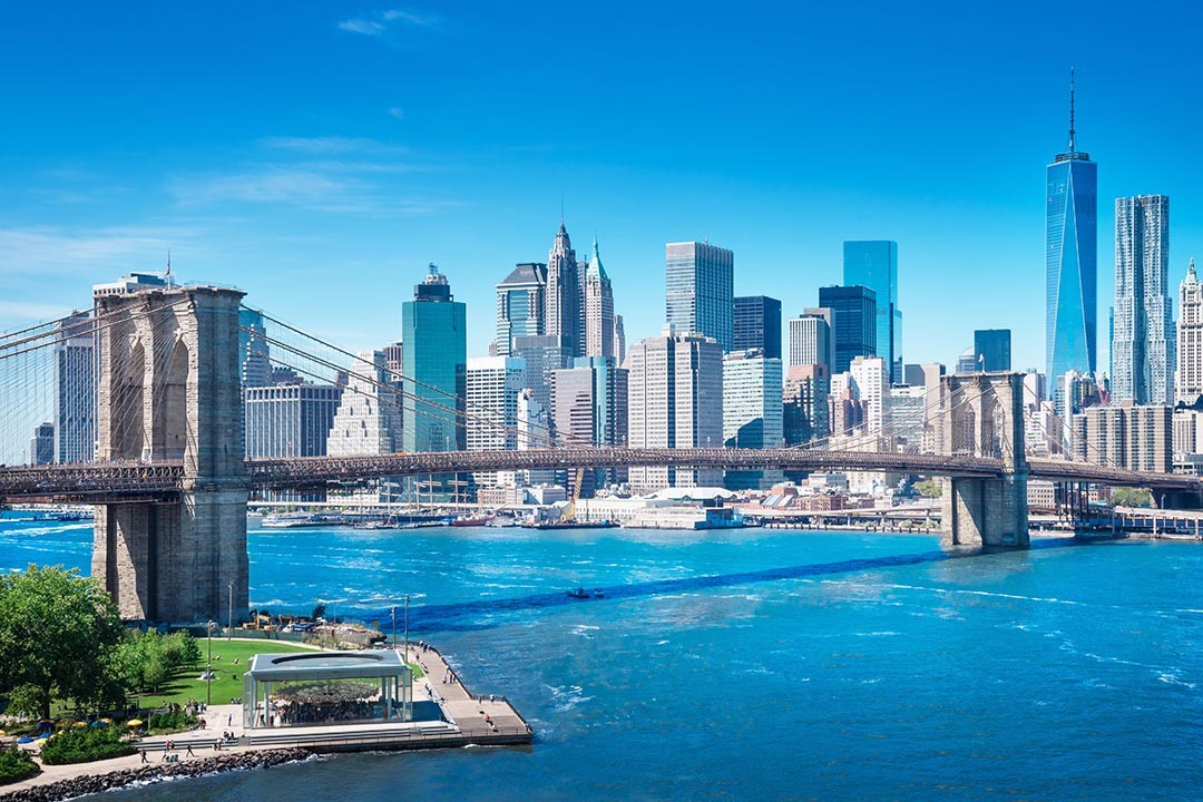The skyline of New York and the Manhattan Bridge on a clear blue sky day.