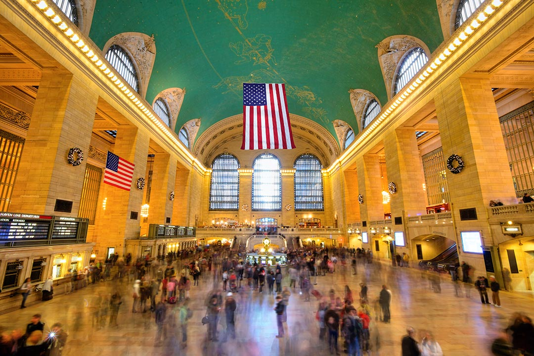 Grand Central Station in New York City with a green ceiling, yellow hued walls, and an american flag hung from the ceiling.