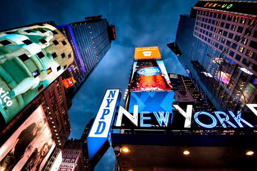 A lit up blue and white sign that reads New York, in Times Square.
