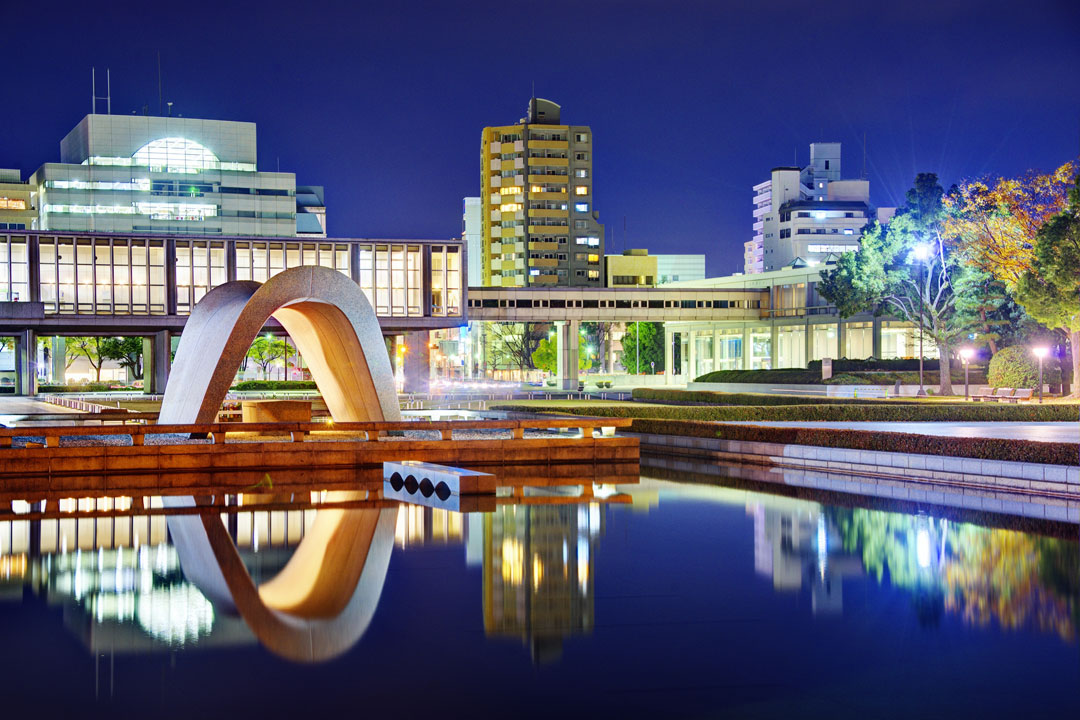 Buildings in Hiroshima lit up in the evening light.