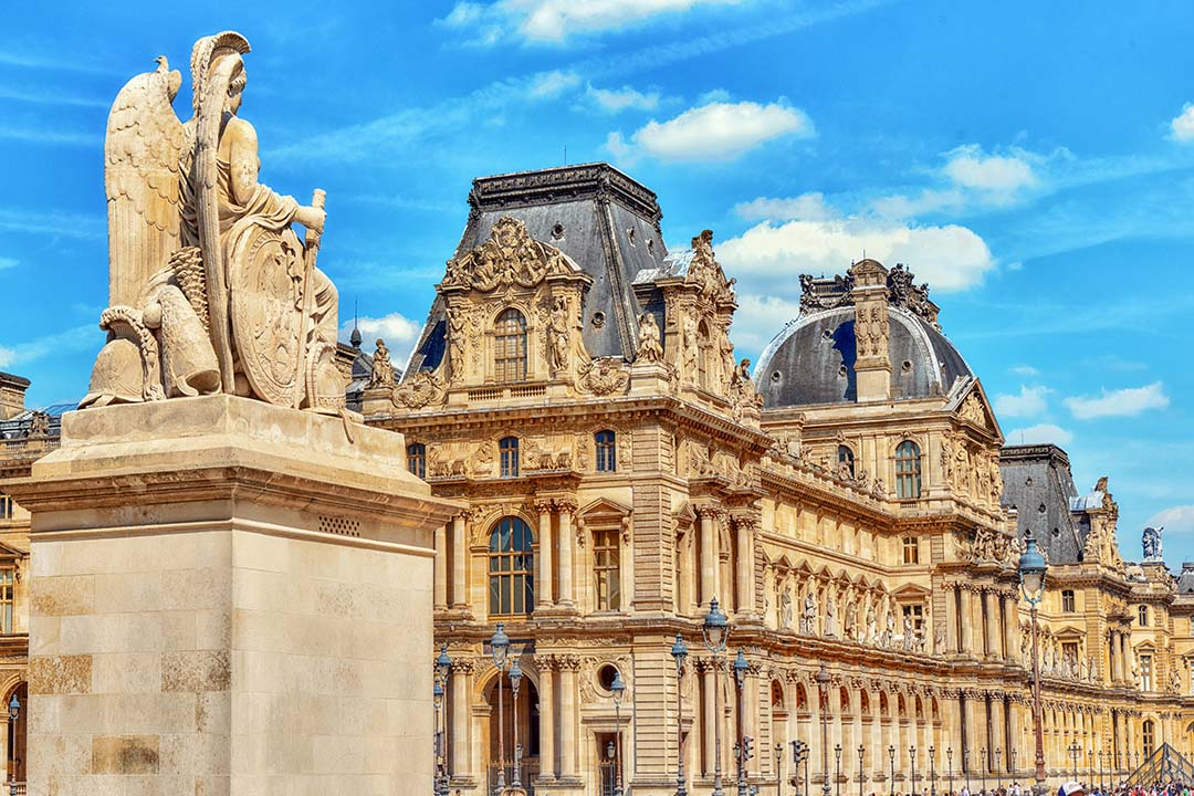Ornate buildings in Paris with a statue at the front.