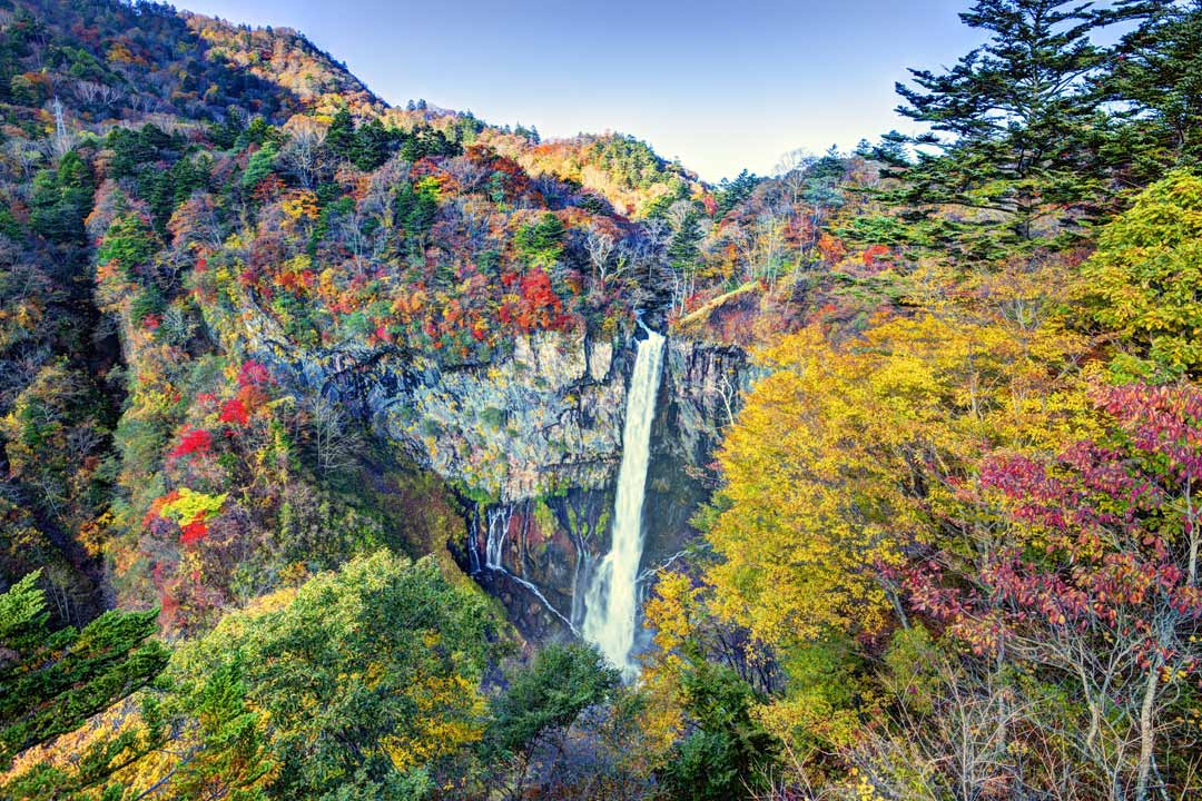 A waterfall flowing over rocks and surroounded by autumn leaves.