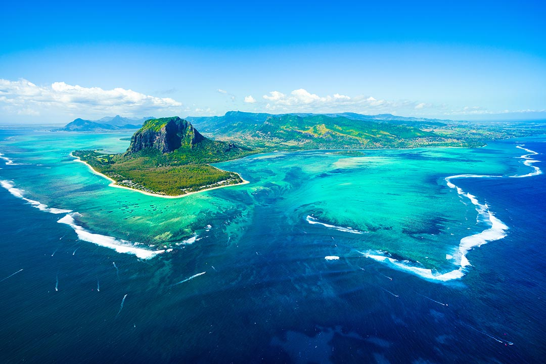 An aerial view of Le Morne Brabant mountain and a beautiful blue lagoon with an underwater waterfall.