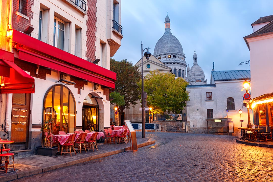 The Place du Tertre with tables of cafe and the Sacre-Coeur in the morning light.