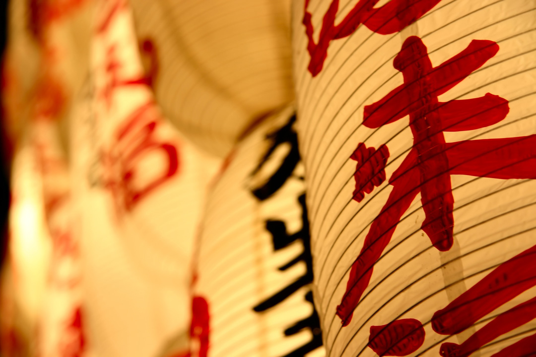 White japanese paper lanterns with red and black japanese writing.