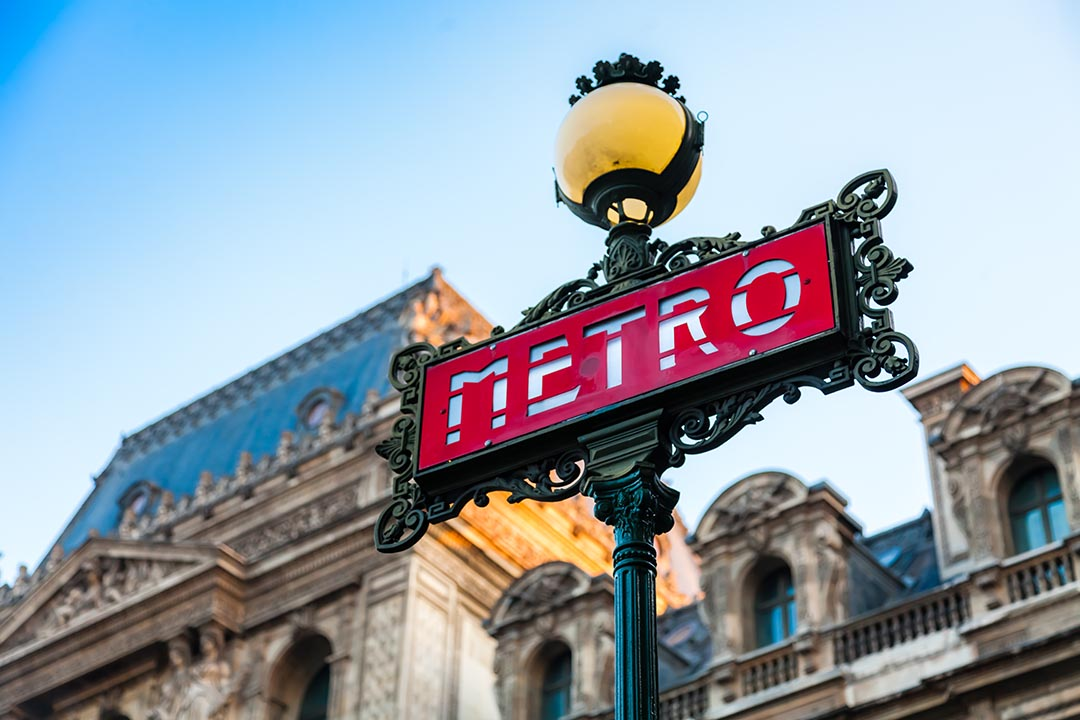 A red Metro transport sign with intricate green decoration around the outside.