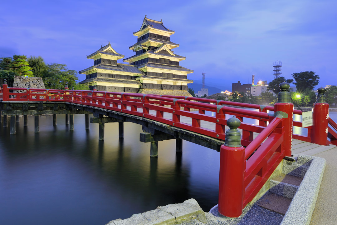 A red wooden bridge crossing over a river towards a 6 tiered temple.