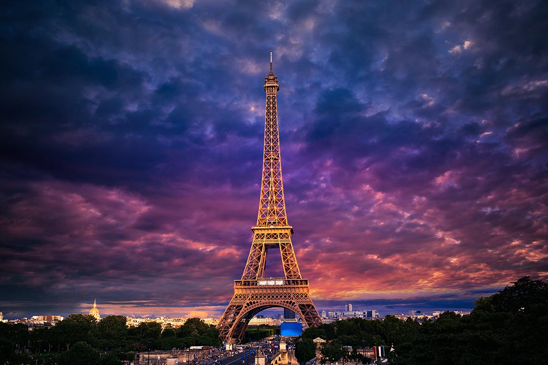 The Eiffel tower in Paris with a purple sunset in the background.