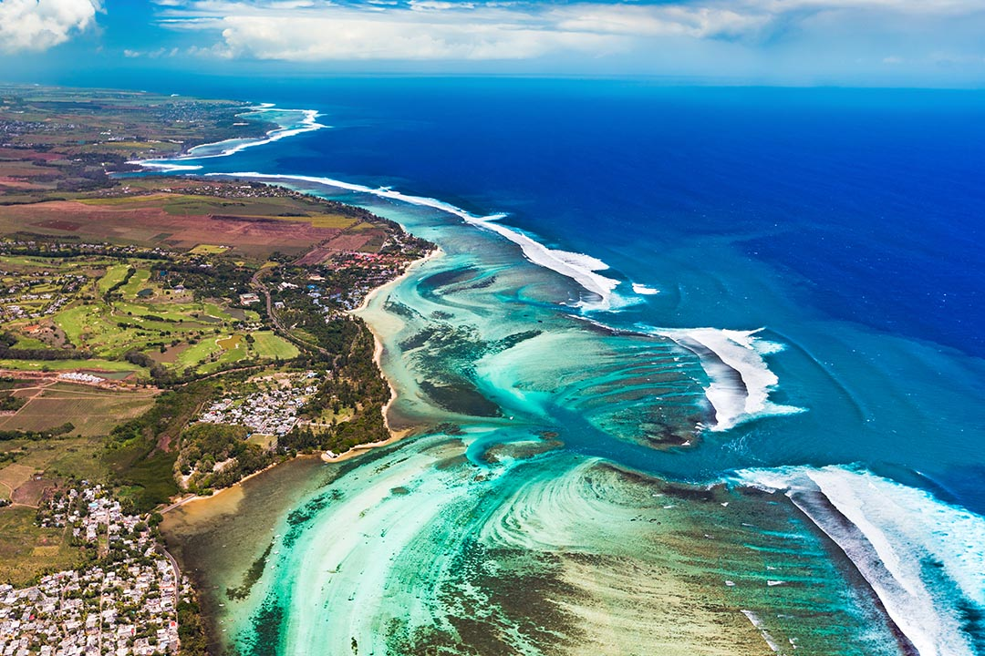 Aerial view of an underwater channel - bright white sands and turquoise water flowing around green and brown coastlines.