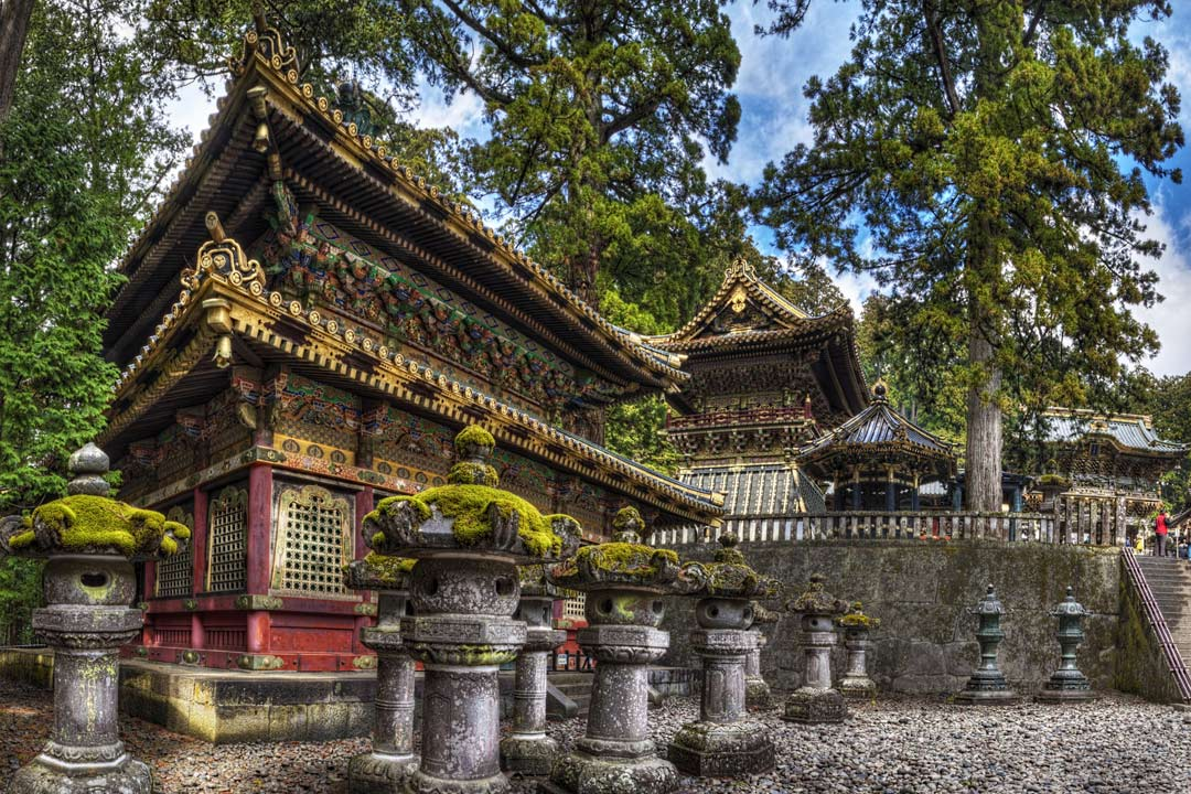 An old temple in Nikko with a moss covered roof and stone statues in the foreground.