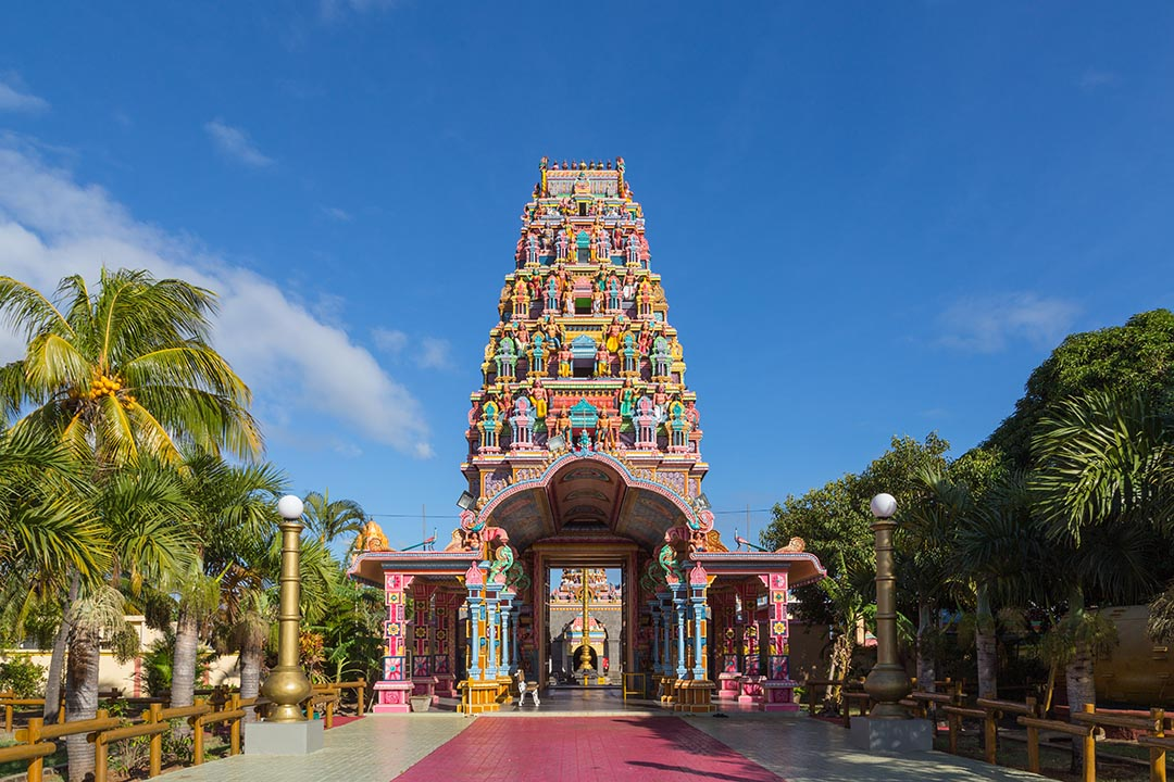Kalaisson Temple in Port Louis Mauritius - a colourful structure with a pink road leading up the the entrance.