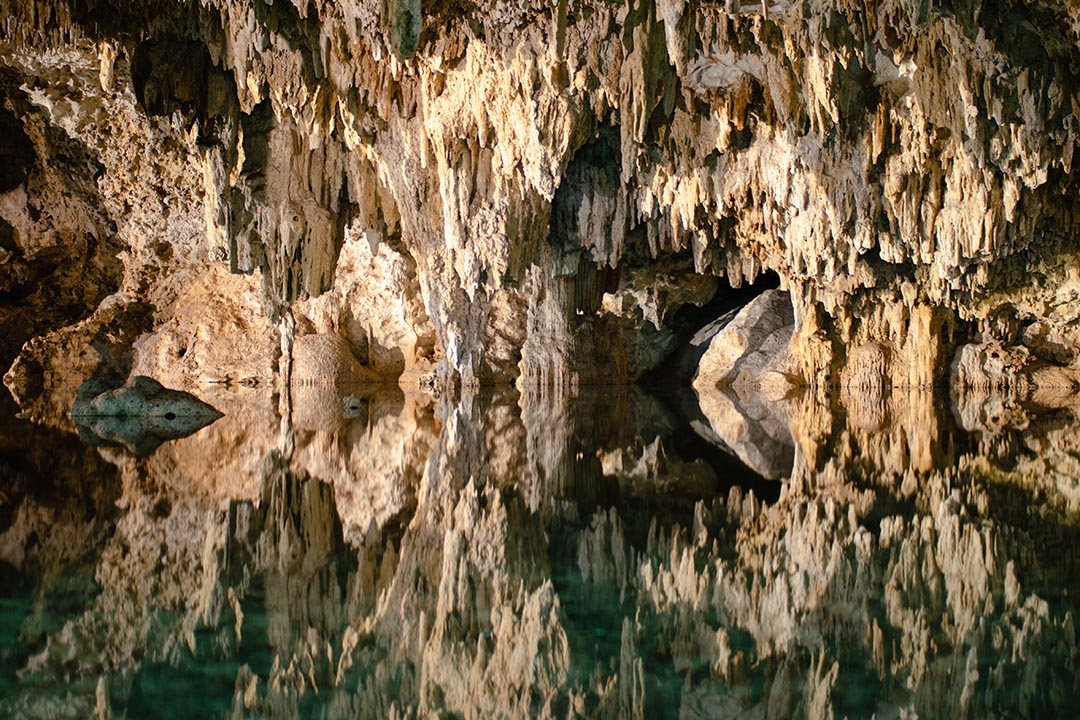 Underground caves reflecting in the blue water.