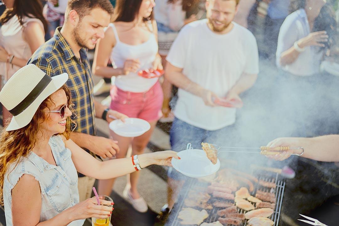 A group of friends enjoying a BBQ at a summer fair.