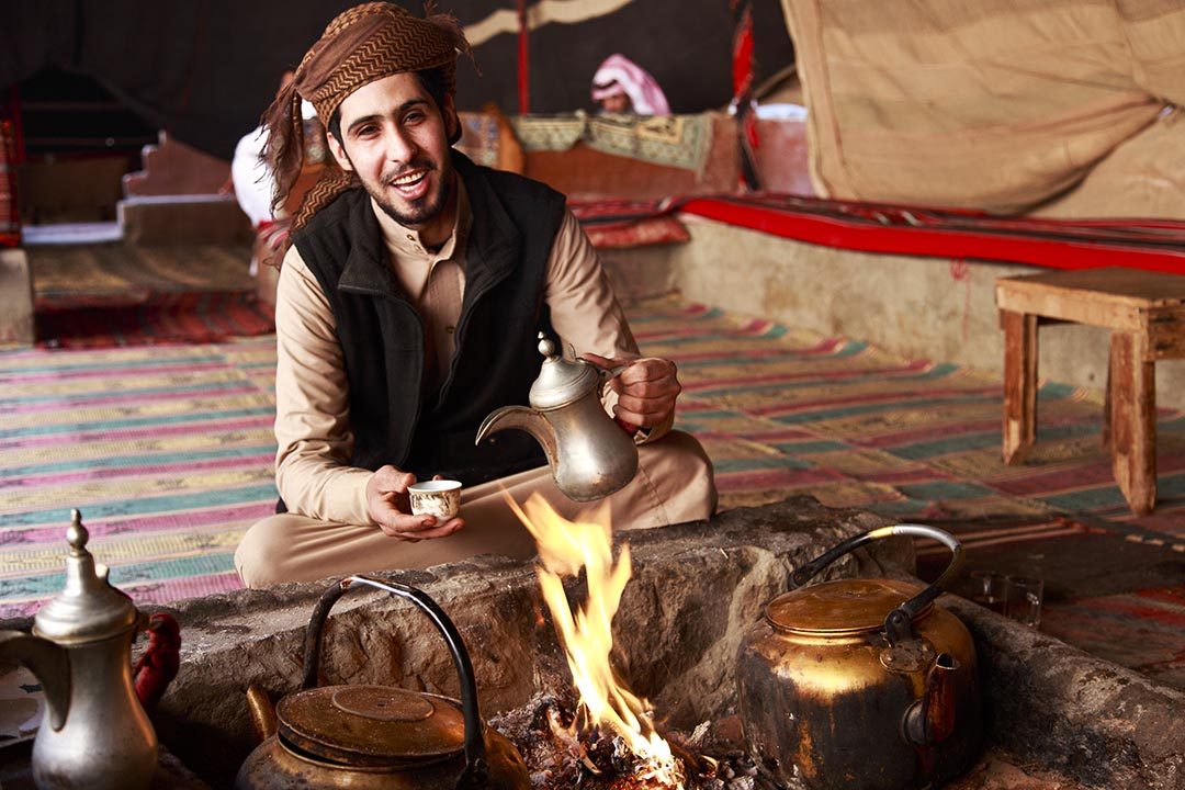 A Bedouin man in Wadi Rum desert welcoming visitors with Arabic Coffee