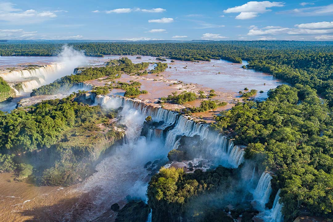 A view of the Iguazu falls from the sky, showing the calm waters on the top before they crash over the edge.