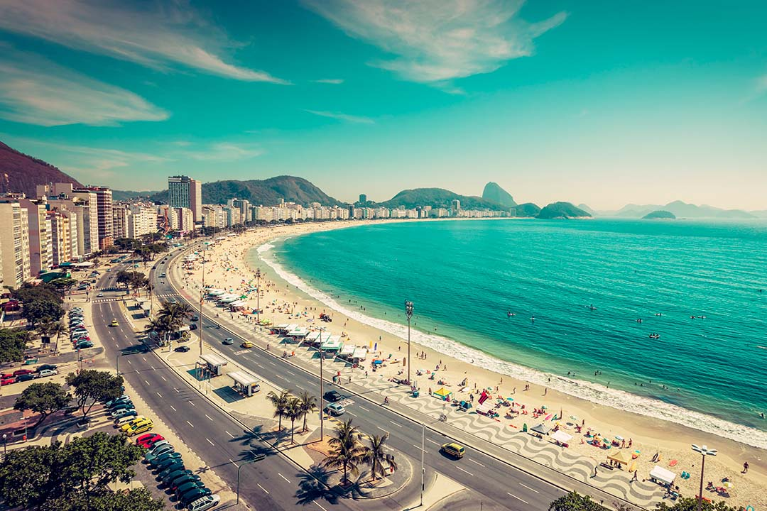 A beach in Rio De Janeiro. Bright blue waters curve round a long strip of sand, with the city to the left.