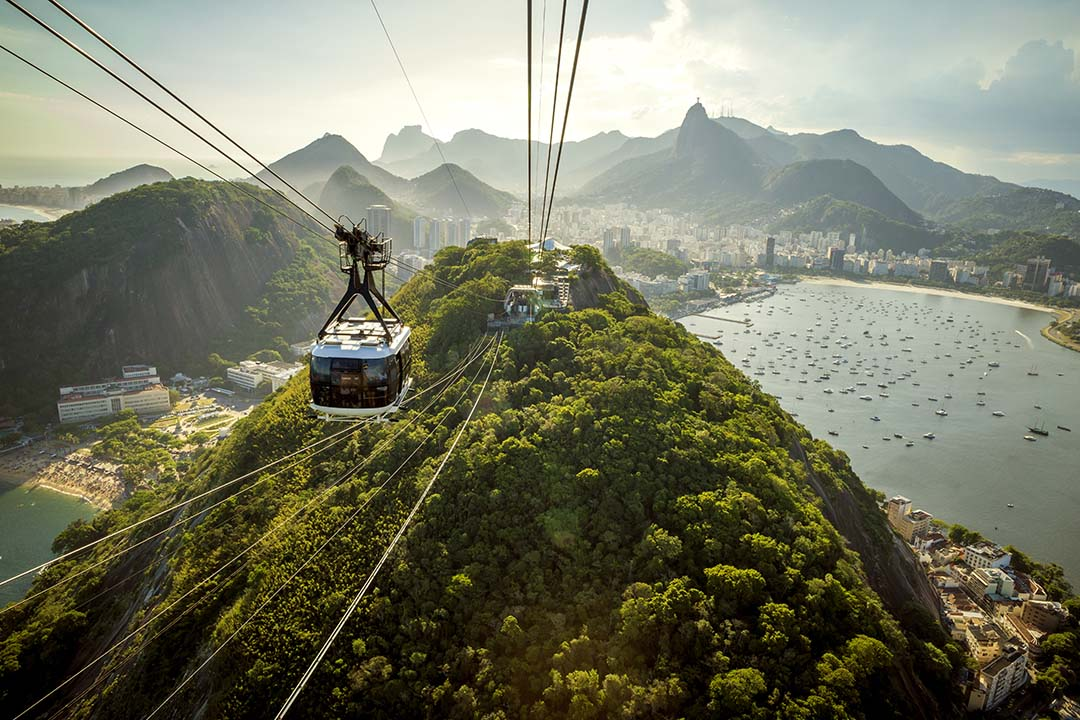 A view of a cable car suspended high above the ground, with lush greenery on a mountain behind.