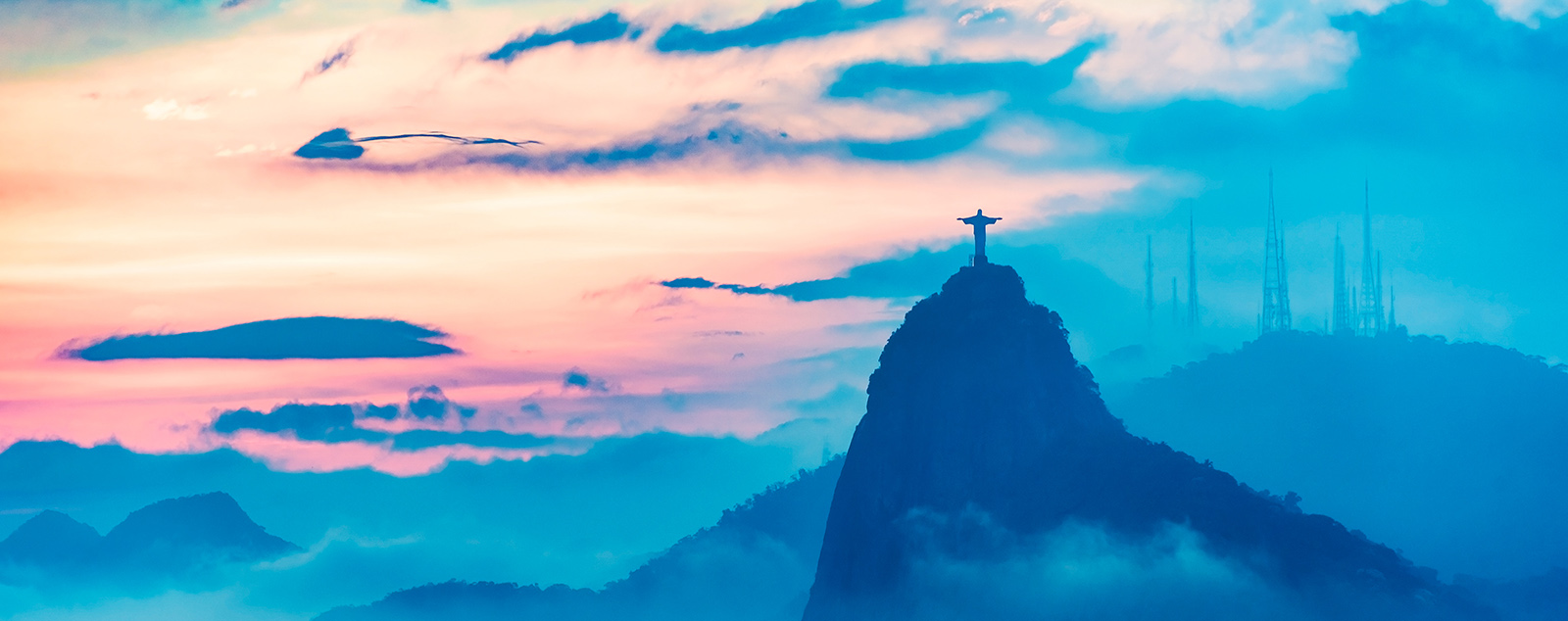 Christ the Redeemer statue stands tall on its mountain top over the city, with a misty blue sky