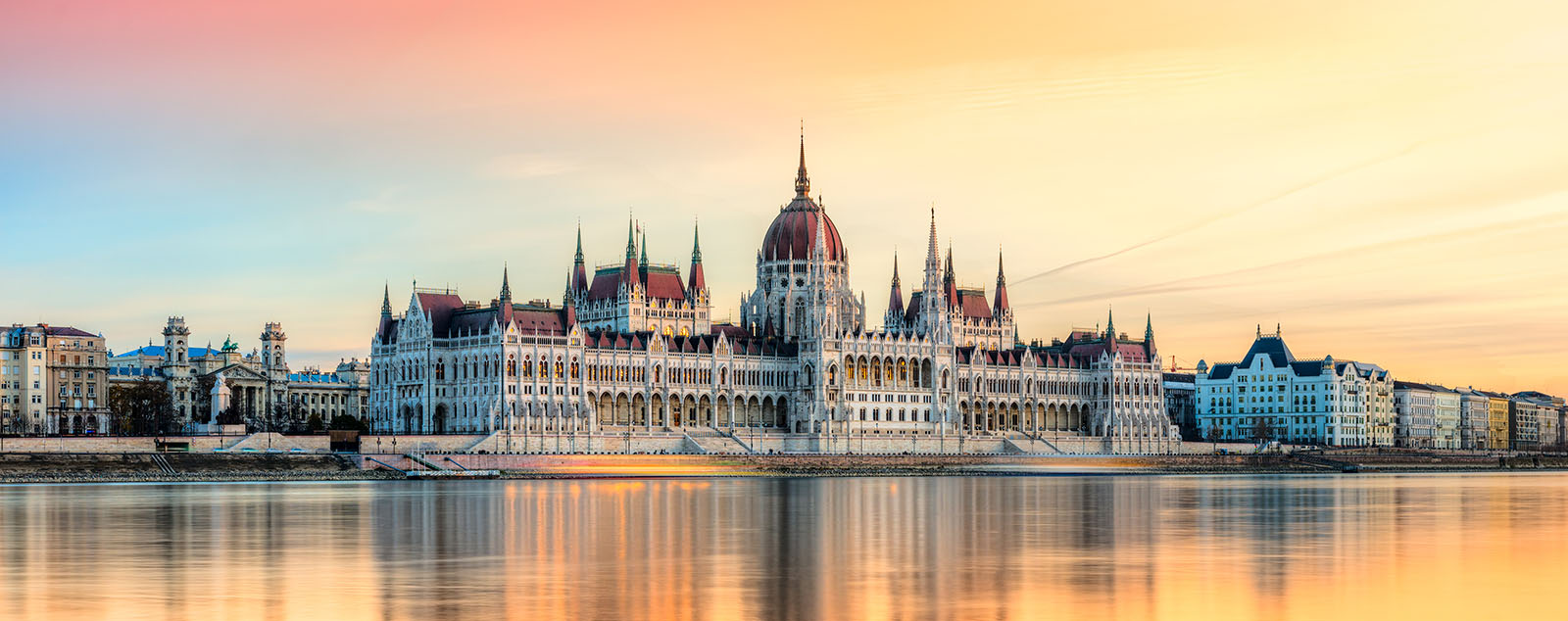 The Parliament Building viewed across the water at sunset, in an orange hue.